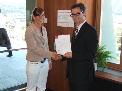 Evi Hilpold, della Cassa Raiffeisen Valle Isarco, riceve il diploma da Stefan Putzer